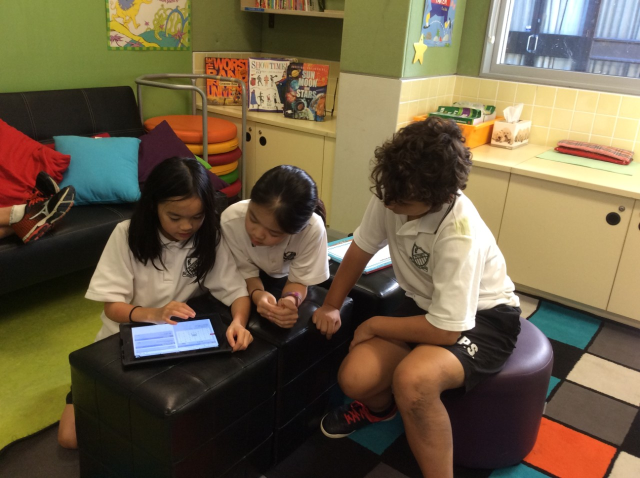 Group of three students working with a tablet to answer some questions.