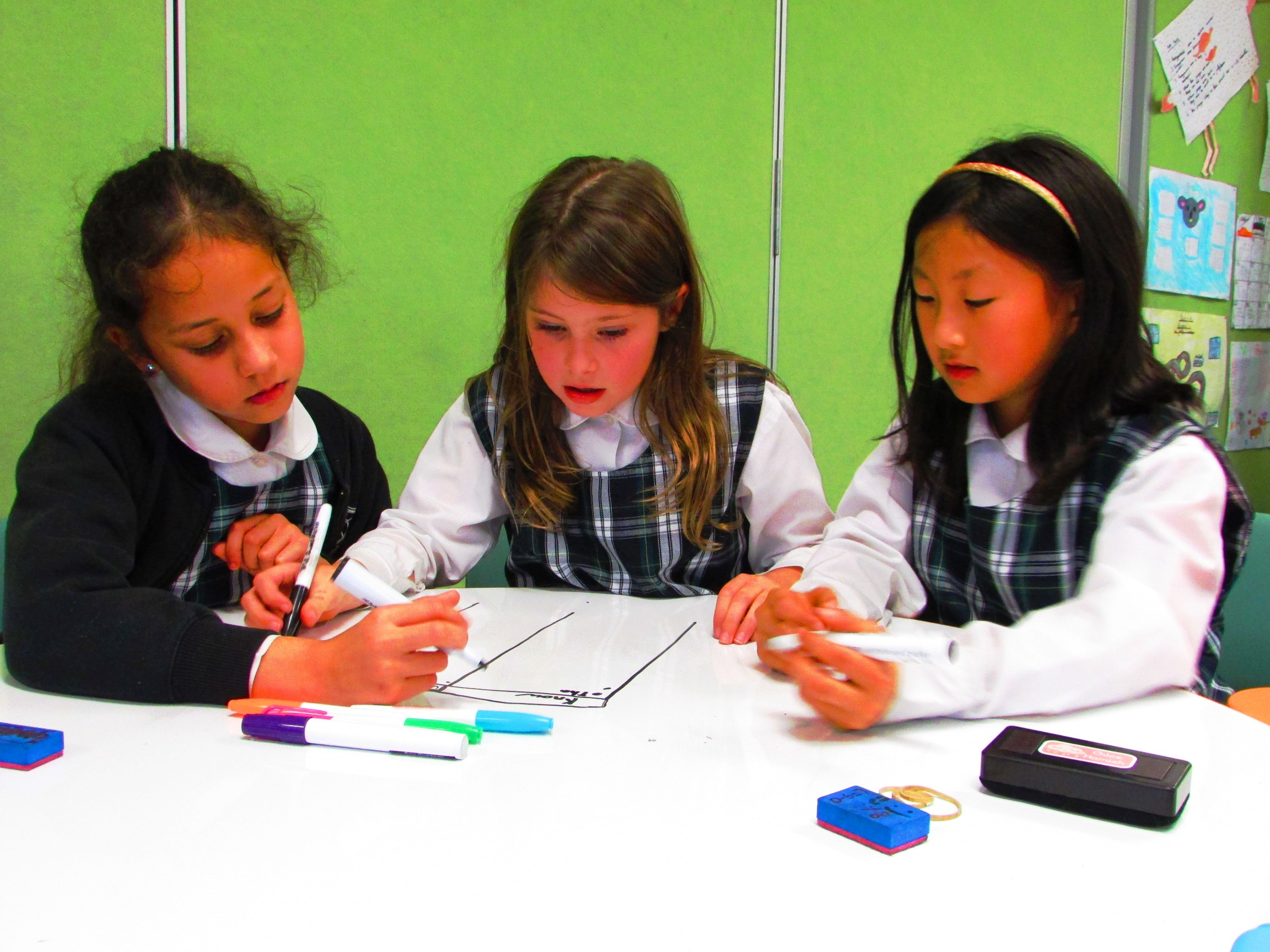 A group of three students working out a problem on a whiteboard table.